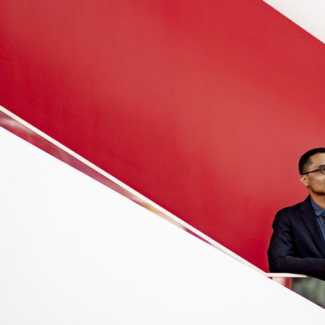 Heath Fogg Davis standing by a staircase with a red background.