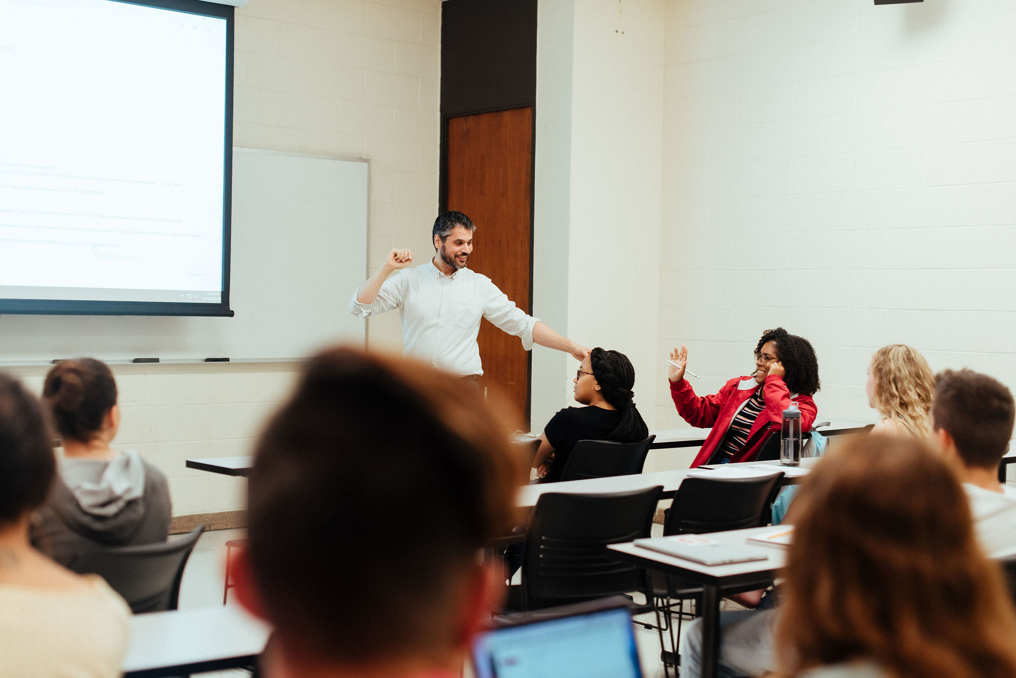professor interacting with students at front of classroom