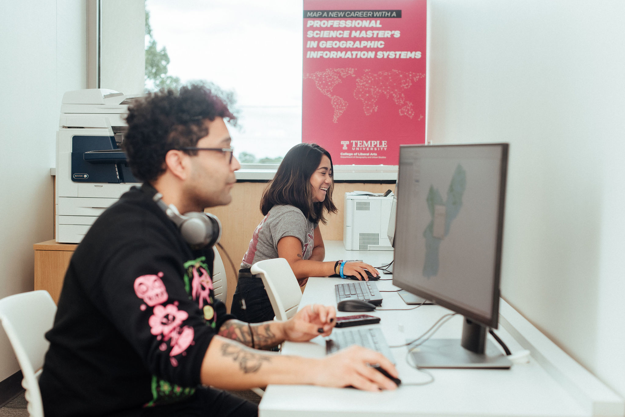 two students at computer work stations in gis lab