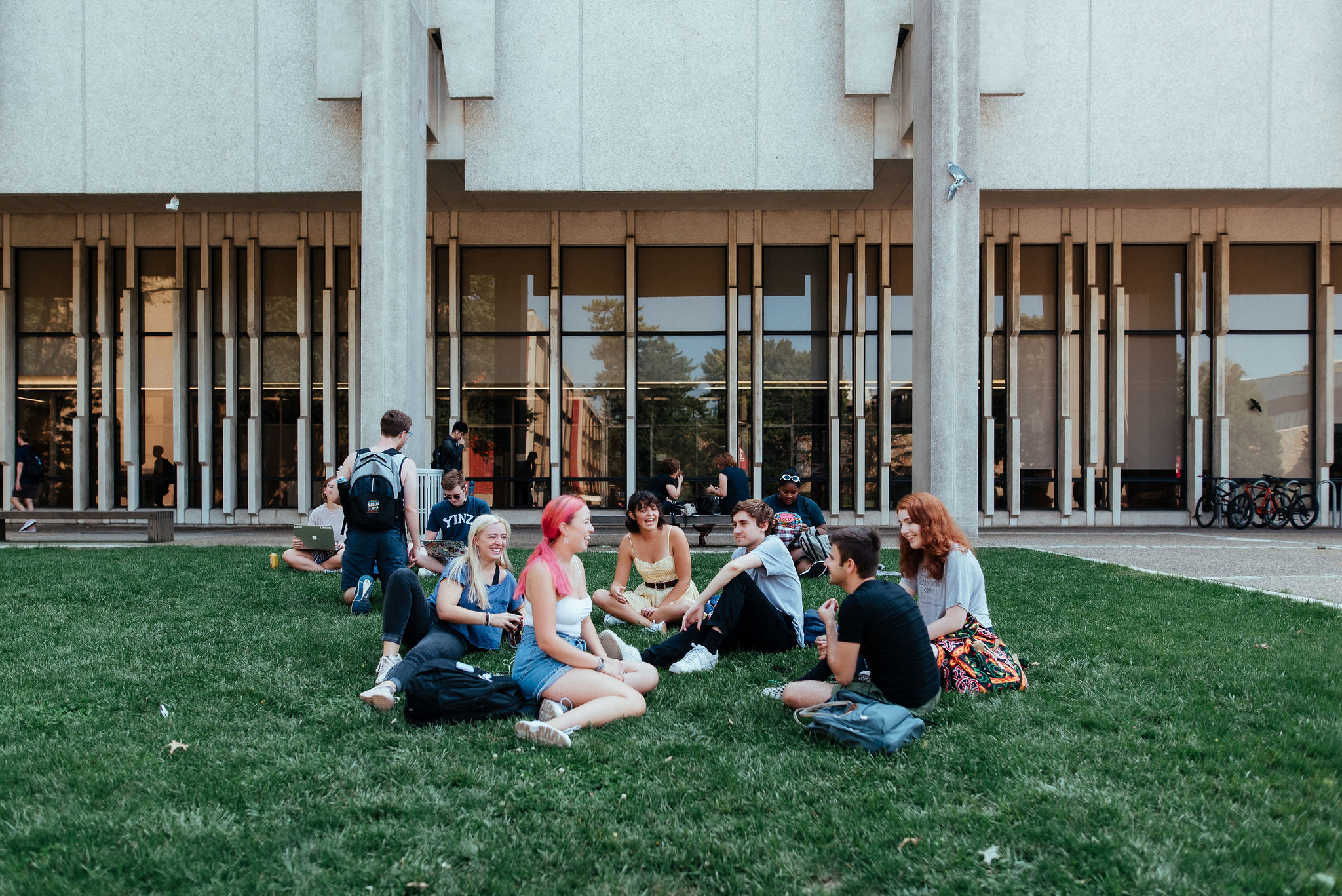 students talking in group while sitting on the grass