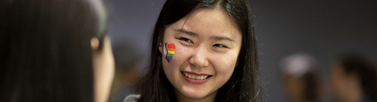 photo of student with pride flag sticker on their cheek