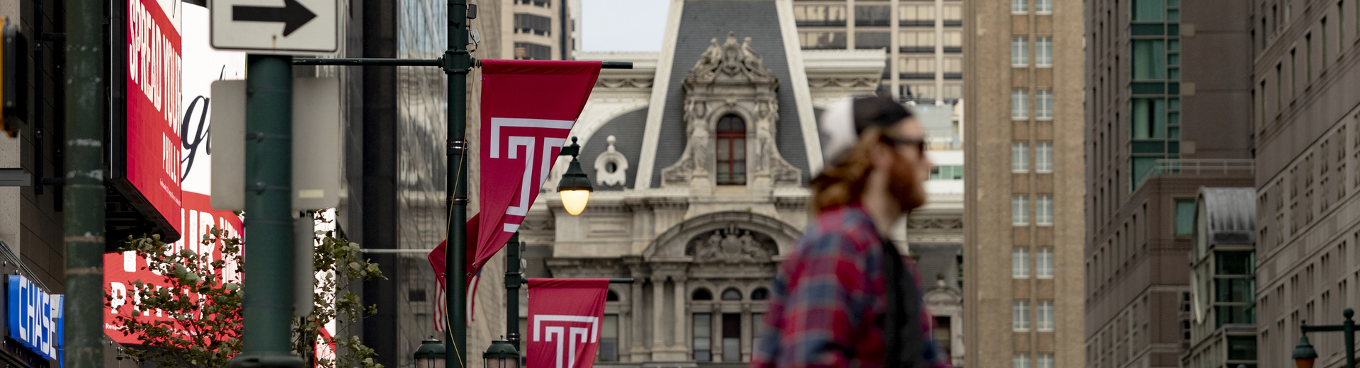 photo of city hall with temple flags and student in foreground