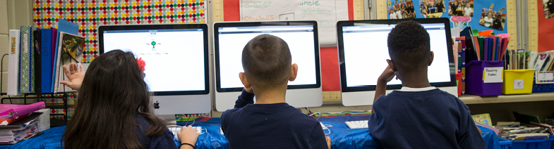 photo of three child students on computers