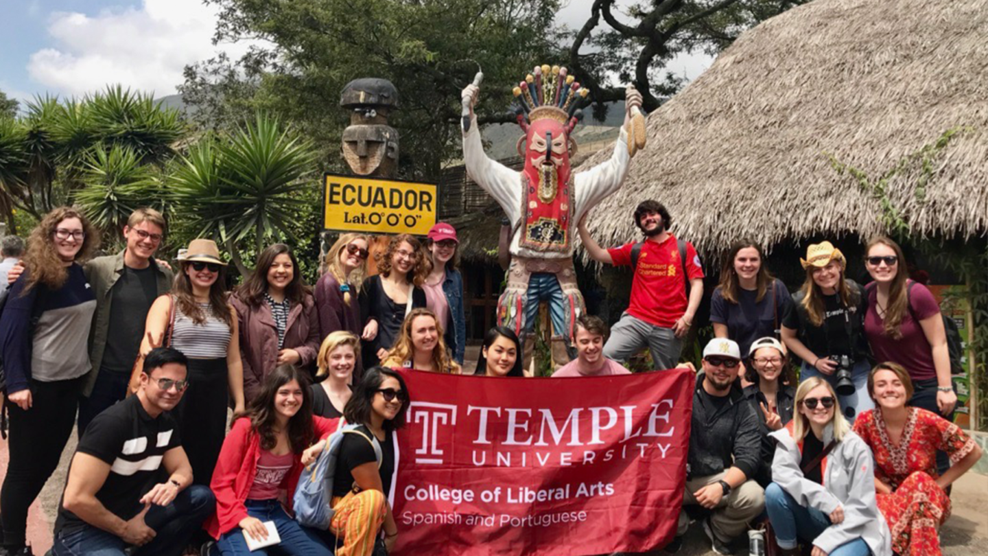 Latin American Studies Students hold College of Liberal Arts banner while abroad in Ecuador